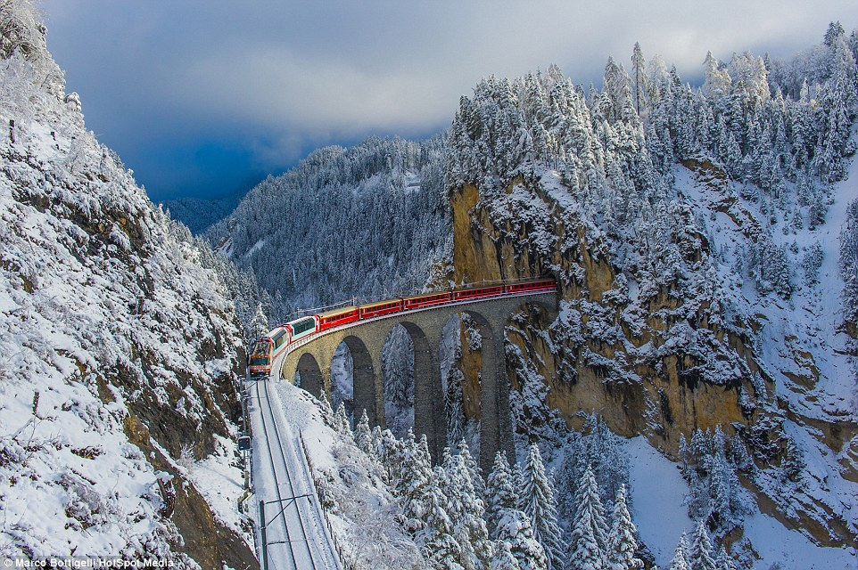 Rolling-across-a-213-foot-high-viaduct-in-the-Alps-the-red-carriages-of-the-Bernina-Express-add-a-splash-of-colour-to-the-spectacular-snow-covered-Swiss-surroundings.jpg