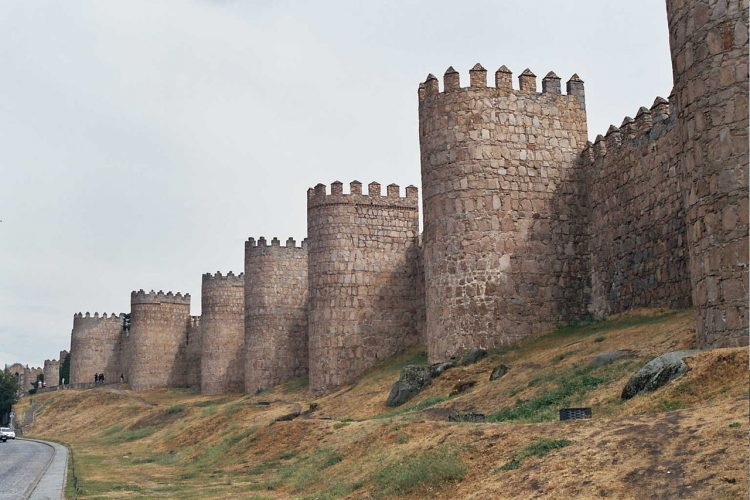 The Walls of Avila is built on the flat summit of a rocky outcrop which rises abruptly in the middle of a vast treeless plain strewn with immense grey boulders and surrounded by lofty mountains.