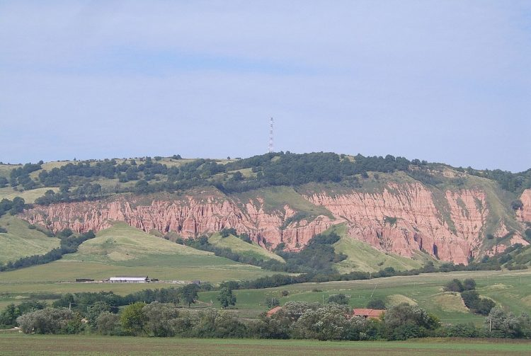 Romania's interrupted by a jagged red anomaly is guarded by the steep walls of the Râpa Roșie (Red Ravine).