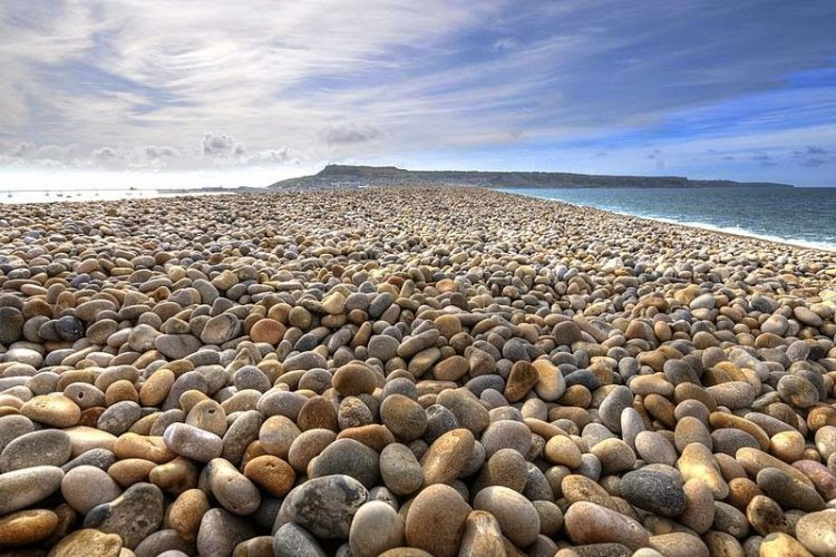 """The English Chesil Beach """"Chesil Bank""""lies in the county of Dorset. It is popular for it's pebbles stretched 18 miles (28 kilometers) long and north-west from Portland to West Bay."""